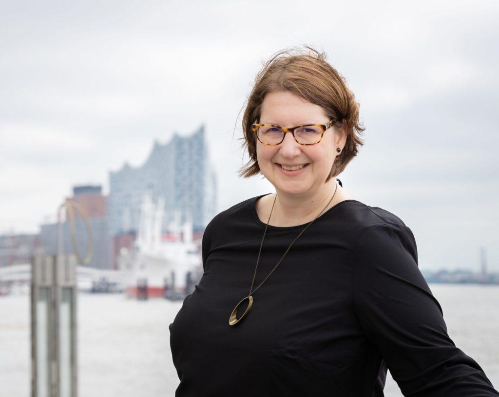 Porträt Kerstin Mayrberger im Hamburger Hafen, Elphi im Hintergrund